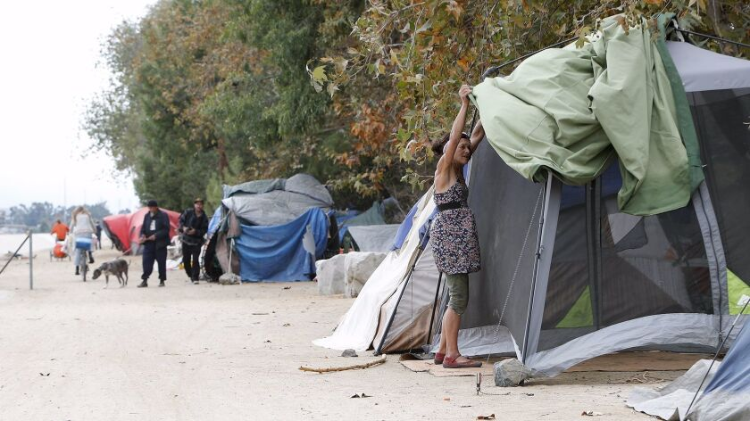 A homeless woman places a cover over her tent along the Santa Ana River Trail in Fountain Valley in 2017, before local officials cleared the county-owned trail.