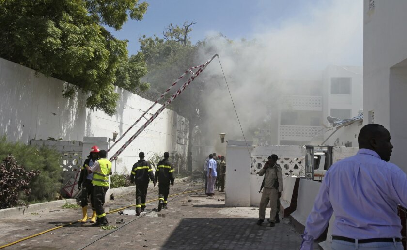 Smoke and steam from fires extinguished with water, clouds the scene of a twin bombing attack on a hotel in the capital Mogadishu, Somalia Friday, Feb. 20, 2015. One person rammed an explosives-laden vehicle into the gate of the Central Hotel in Somalia's capital, and another went through the gates and blew himself up, killing at least four people on Friday including the deputy mayor and a legislator, officials said, while the country's deputy prime minister was also among those wounded by the bombings. (AP Photo/Farah Abdi Warsameh)