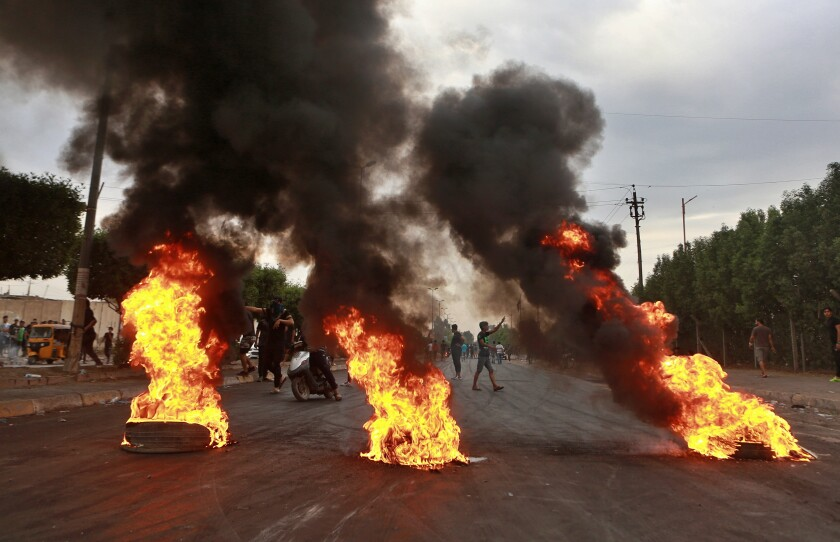 Anti-government protesters set fires and close a street in Baghdad earlier this month, part of a running series of deadly demonstrations over economic stagnation and government corruption in Iraq.
