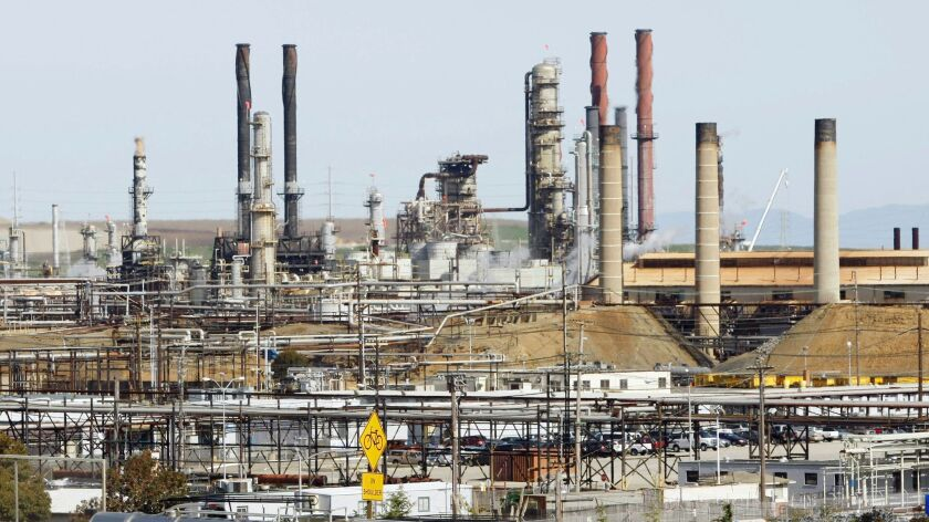 FILE - This March 9, 2010, file photo shows a tanker truck passing the Chevron oil refinery in Richm
