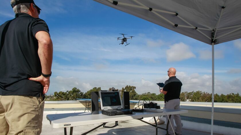 Chula Vista officers on the rooftop of the police station watch a drone come in for landing