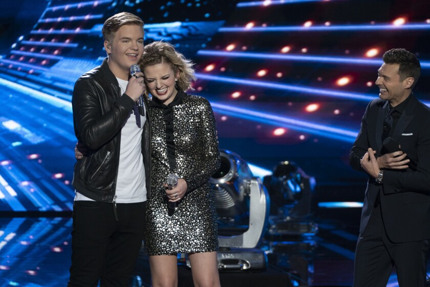 """""""American Idol"""" finalists Caleb Lee Hutchinson and Maddie Poppe await the results from show host Ryan Seacrest on the season finale of ABC's rebooted version of the singing competition on May 21, 2018."""