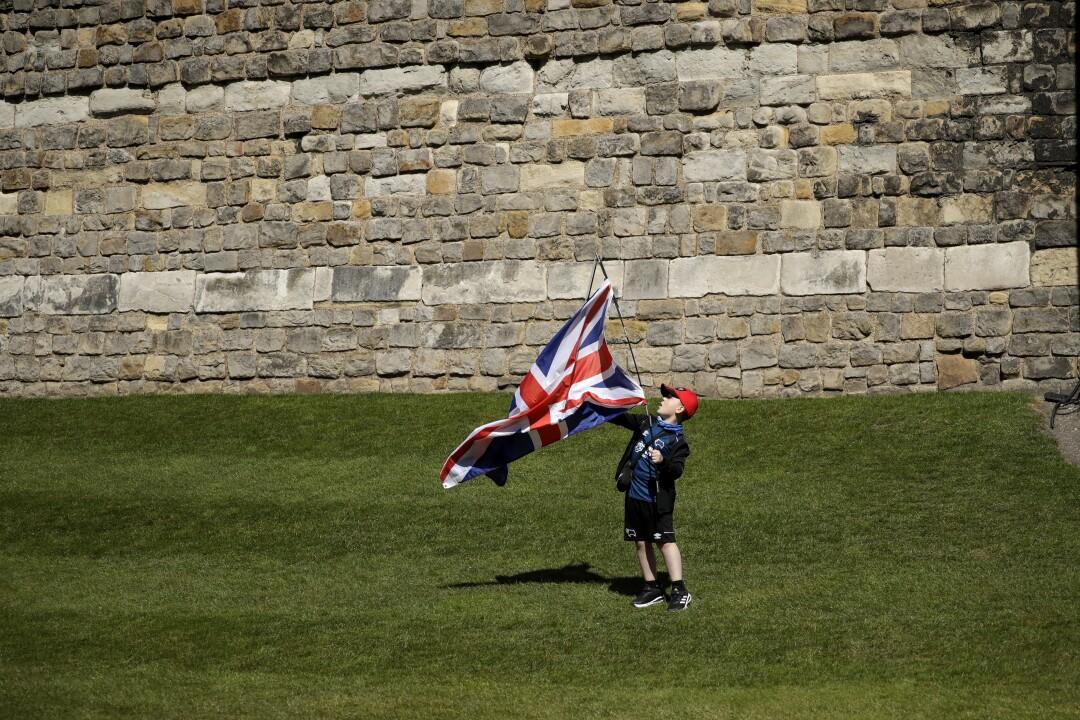 Jayden, 8, holds a Union Jack outside Windsor Castle on the grass.