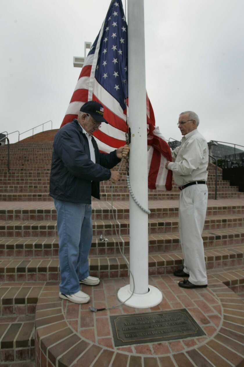 Ralph Cummings, left, and Bob Phillips raised the flag yesterday at the Mount Soledad Veterans Memorial.