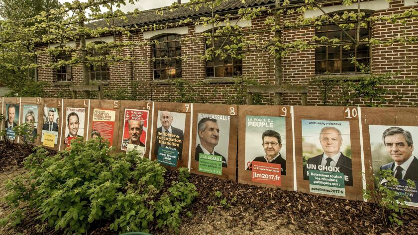 Campaign posters of French presidential candidates hang outside a church in Le Ryveld hamlet in Steenvoorde, northern France, on April 21, 2017.