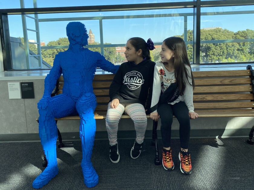 """A Lego man in blue sits with visitors at the California Science Center's """"The Art of the Brick."""""""