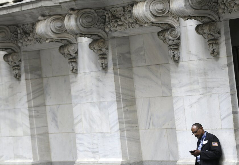 FILE - In this Monday, Aug. 24, 2015, file photo, a trader looks at his phone outside the New York Stock Exchange, as world stock markets plunged after China's main index sank to its biggest drop since the early days of the global financial crisis. The slide on Wall Street could damage public-employee pension funds around the country that have yet to recover from the Great Recession. Since the start of 2016, stocks have been down by about 8 percent. (AP Photo/Seth Wenig, File)