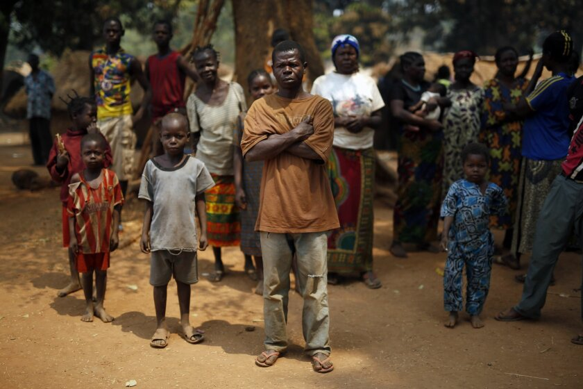 Christian families living in a refugee camp stand under a tree in Kaga-Bandoro, Central African Republic, Tuesday Feb. 16,  2016.  Refugees in the north of Central African Republic say they hope the new president will bring peace but no one is heading home just yet. Thousands are still living in di