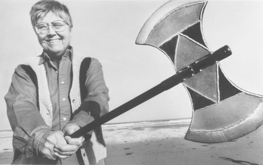 Mary Daly holds a double-headed ax, a symbol that modern-day feminists link to Amazon warriors and lesbian and feminist strength. Daly repeatedly challenged the Boston College establishment until a legal case led to her retirement.