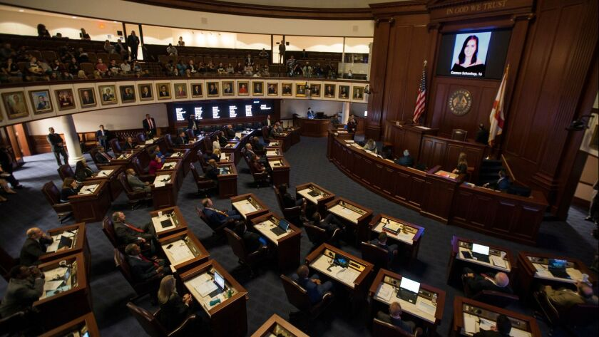 FILE - In this Feb. 21, 2018, file photo, the Florida Senate chamber is darkened while a slideshow s