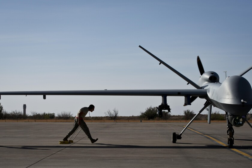 After taxiing in an MQ-9 Reaper, Airman 1st Class Jon Mann walks under a Reaper's wing at Holloman Air Force Base, N.M.