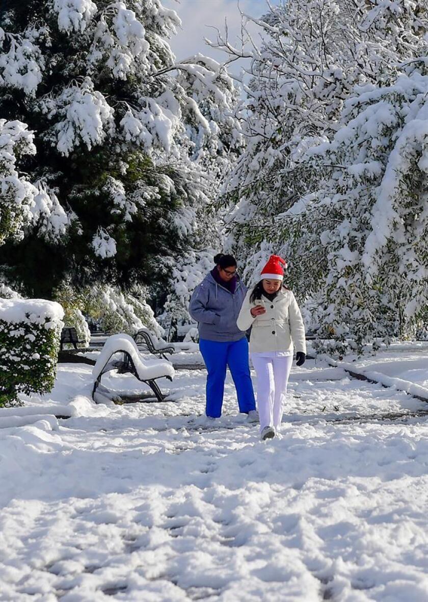 Fotografía de archivo fechada el día 8 de diciembre de 2017, que muestra a dos personas mientras caminan en un parque cubierto de nieve, en la Ciudad de Saltillo en Coahuila (México). EFE/Archivo
