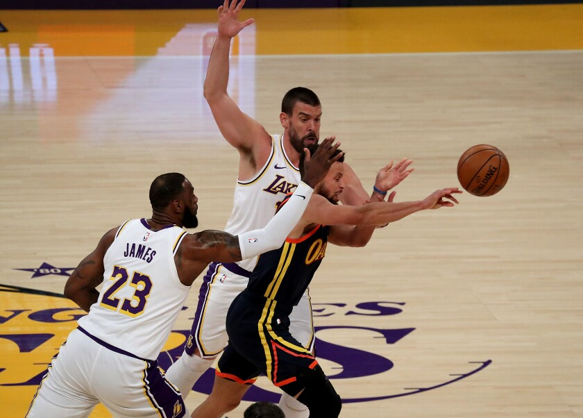 Lakers LeBron James and Marc Gasol try to trap Warriors guard Stephen Curry.