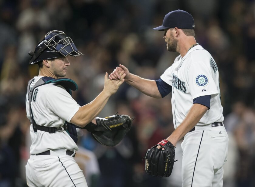 Seattle Mariners pitcher Tom Wilhelmsen, right, is congratulated by catcher Mike Zunino after Wilhelmsen earned a save in a baseball game against the Oakland Athletics, Tuesday, Aug. 25, 2015, in Seattle. The Mariners won 6-5. (AP Photo/Stephen Brashear)