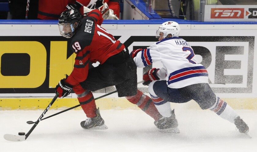 Jordan Harris of the U.S., right, chases Canada's Quinton Byfield on the ice during the world junior championships Dec. 26.