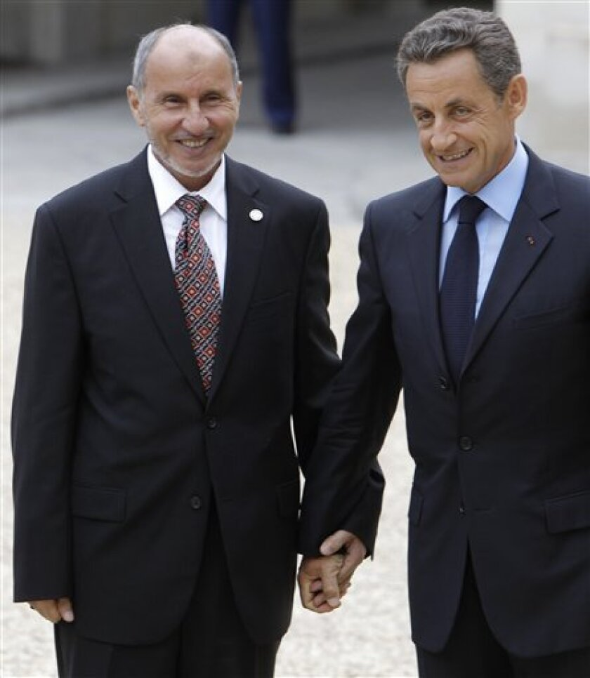 French President Nicolas Sarkozy, right, holds the hand of Libyan National Transitional Council chairman Mustafa Abdel Jalil, at the Elysee Palace in Paris, Thursday, Sept.1, 2011. Heads of state and top officials gather in Paris to work out how to support Libya's opposition leaders after Gadhafi's fall from power. (AP Photo/Jacques Brinon)