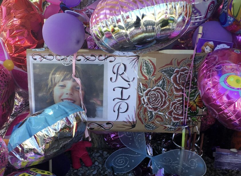 A picture of Victoria Martens, a 10-year-old Albuquerque girl brutally murdered last week, is placed in a memorial outside her former Albuquerque apartment on Monday, Aug. 29, 2016. Stricken with grief, the grandparents and other family members of Martens, who was brutally slain last week, clutched