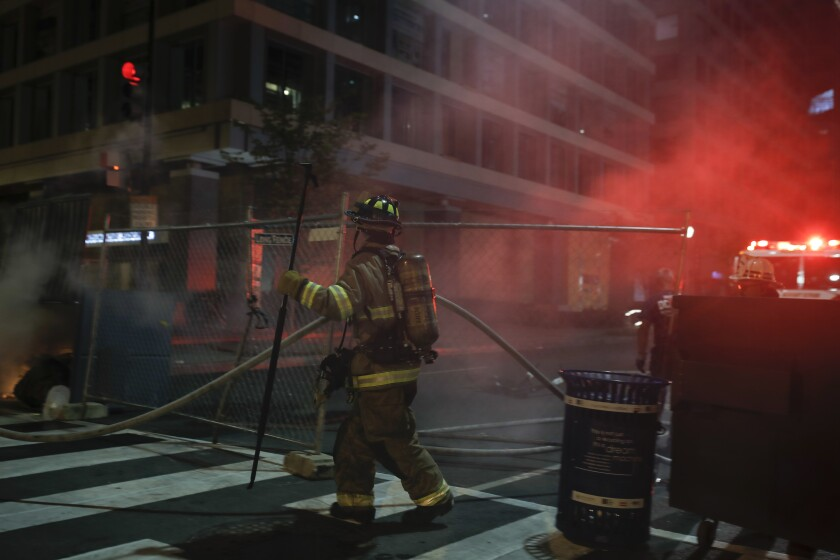 Firefighters put out a dumpster fire as protesters and police gather at Lafayette Park.