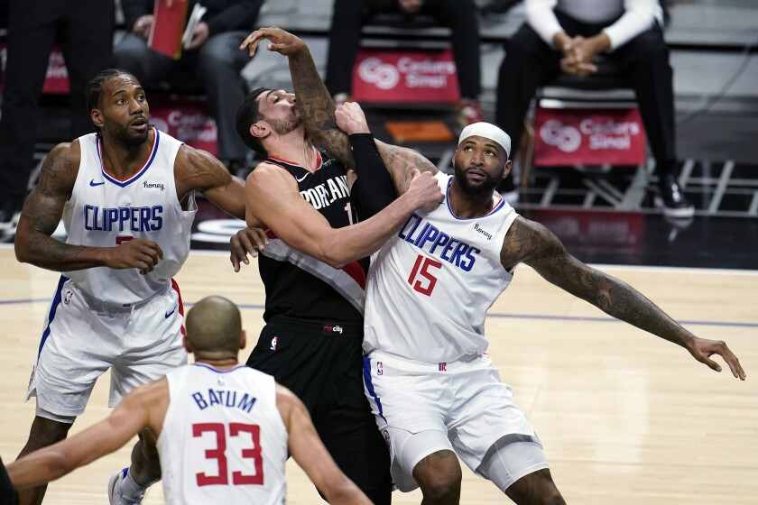 Clippers center DeMarcus Cousins works for position in the lane against rail Blazers center Enes Kanter.