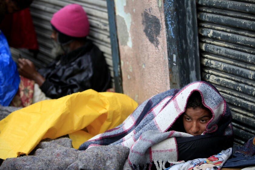 A man tries to keep warm under blankets on skid row.