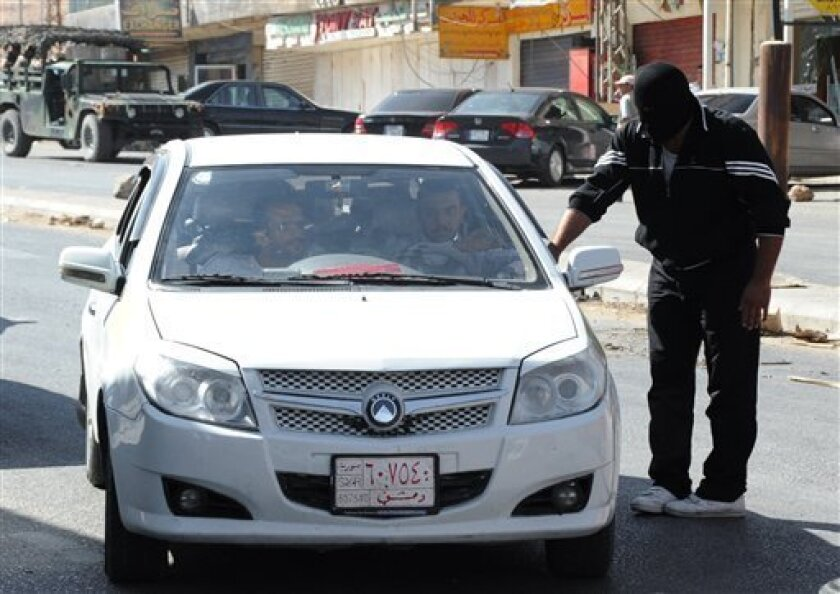A masked man from a Sunni group who blocked a road linked to the Lebanese-Syrian border, checks a Syrian car which carries Syrian passengers, in Masnaa, eastern Lebanon, Thursday, Aug. 16, 2012. Masked Lebanese believed to be from the town of Majdal Anjar, notorious for harboring Sunni fundamentali