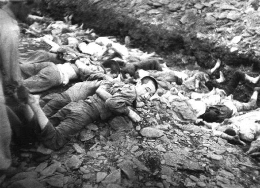 "FILE - In this July 1950 U.S. Army file photograph once classified ""top secret,"" prisoners lie on the ground before their execution by South Korean troops in Taejon, South Korea. Shutting down its inquiry into South Korea's hidden history, a government commission investigating a century of human ri"