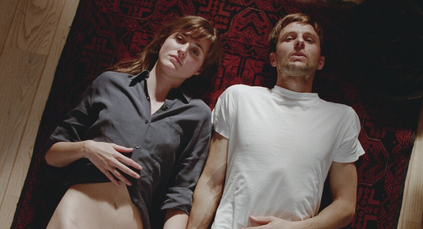 A partially unclothed woman and a man lie on the floor.