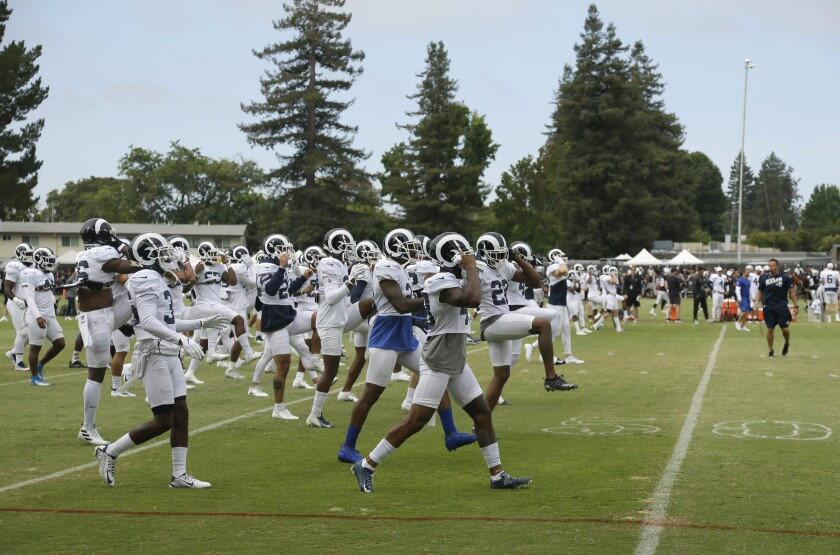 The Rams warm up during training camp. The team will take on the Dallas Cowboys in a preseason game on Saturday in Hawaii.