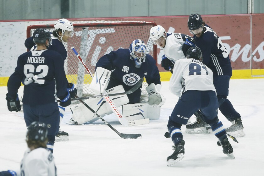 Winnipeg Jets goaltender Eric Comrie (1) saves the shot during their NHL hockey training camp practice in Winnipeg, Manitoba, Wednesday, Jan. 6, 2021. (John Woods/The Canadian Press via AP)