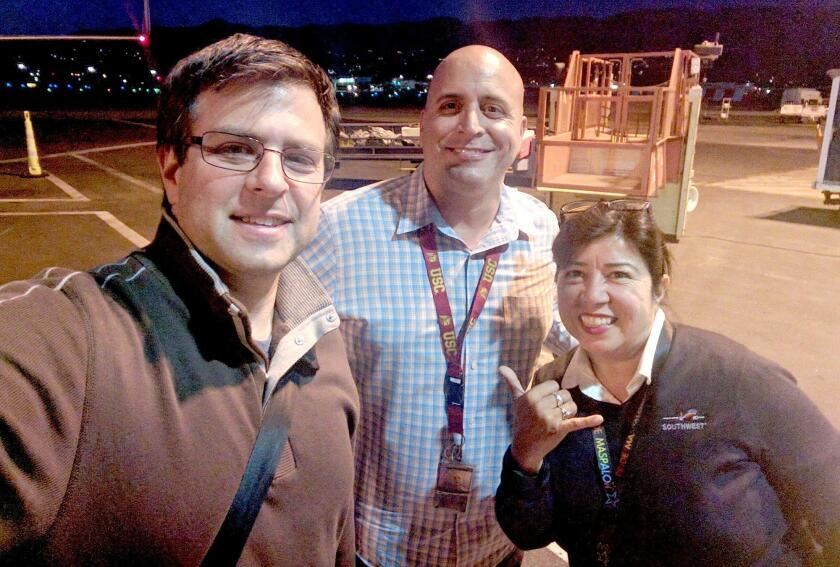 Long Beach resident Brett Snyder takes a selfie with Southwest Airlines employees at Hollywood Burbank Airport Tuesday night. Snyder, writer of the Cranky Flier aviation blog, accomplished the feat to commemorate the 10th anniversary of his blog.