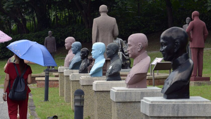Tourists pass statues of the late Nationalist leader Chiang Kai-shek at a park in Taoyuan, northern Taiwan. Tributes to Taiwan's former leader would be removed across the island under legislation approved by lawmakers.