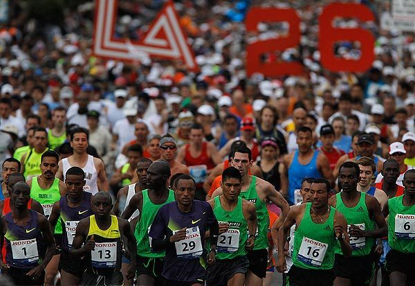 Elite competitors lead a pack of thousands of runners at the start of the L.A. Marathon at Dodger Stadium.