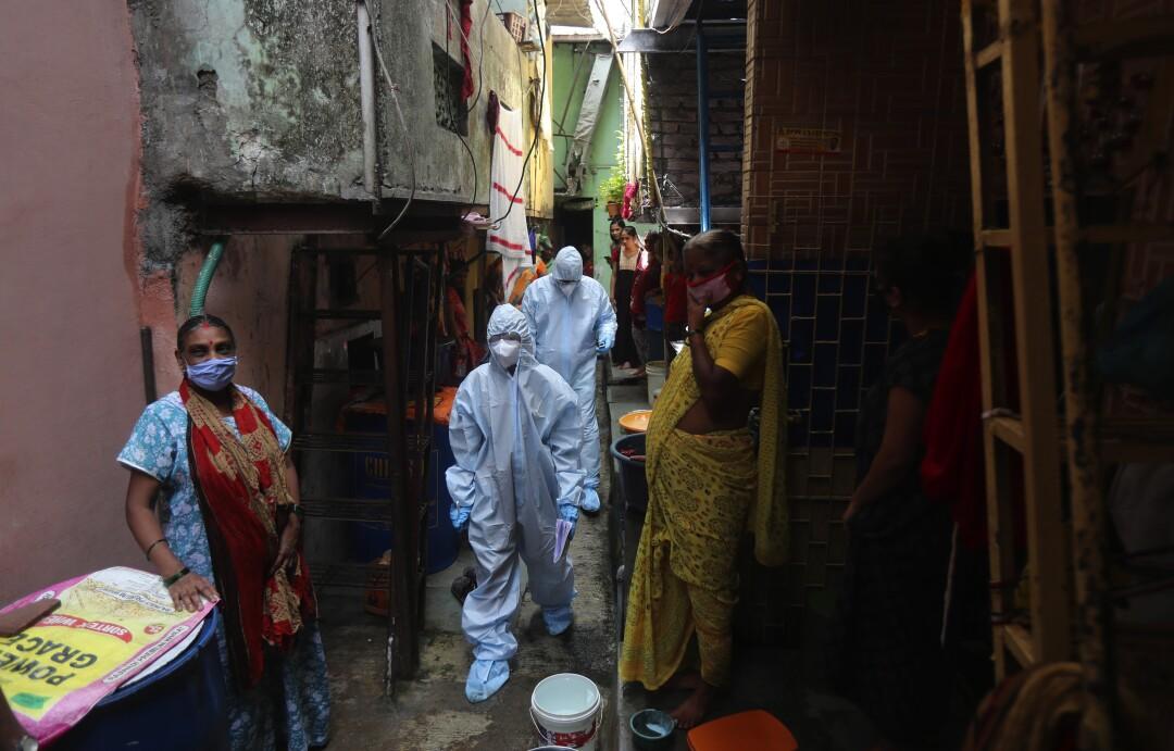 Health workers walk through Dharavi on June 20.