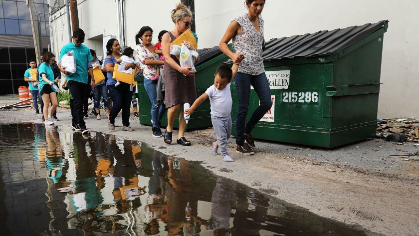 Volunteers walk dozens of women and their children to a relief center following their release from Customs and Border Protection on June 22 in McAllen, Texas.