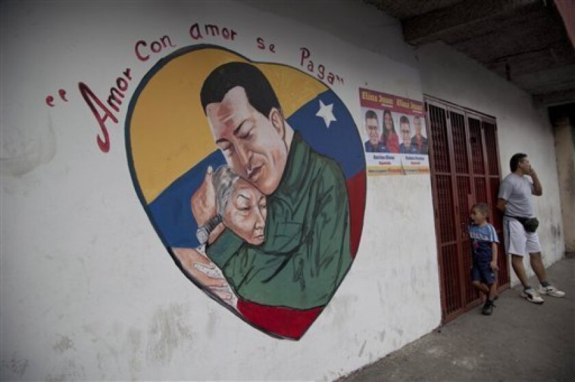 """A heart-shaped mural shows an image of Venezuela's President Hugo Chavez hugging a woman in Caracas, Venezuela, Friday, Jan. 4, 2013. Chavez hasn't spoken publicly or been seen since his Dec. 11 operation in Cuba, and the latest report from his government Thursday night increased speculation that he is unlikely to attend his Jan. 10 inaugural ceremony. The message above the mural reads in Spanish; """"Love is repaid with love."""" (AP Photo/Ariana Cubillos)"""