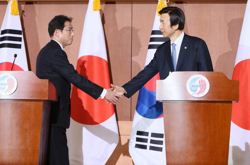 Japanese Foreign Minister Fumio Kishida, left, and his South Korean counterpart, Yun Byung-se, shake hands during a news conference in Seoul after announcing a deal concerning the so-called comfort women of World War II.