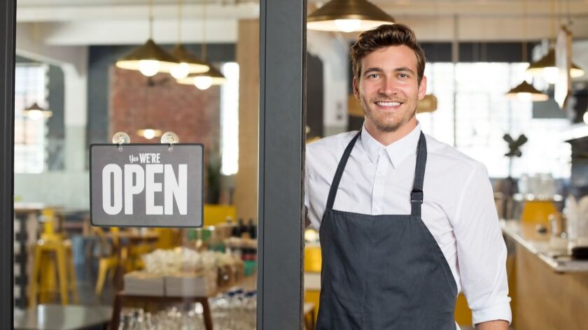 Portrait of smiling owner standing at his restaurant gate with open signboard. Young entrepreneur le