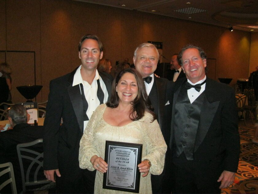 Jerry and Janet Klein, center, show off their 'Retailer of the Year' award at the International Formalwear Association convention.