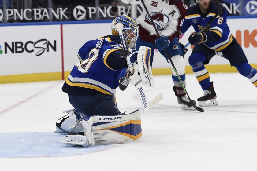 St. Louis Blues' Jordan Binnington (50) blocks a shot from the Colorado Avalanche during the first period of an NHL hockey game on Wednesday, April 14, 2021, in St. Louis. (AP Photo/Joe Puetz)