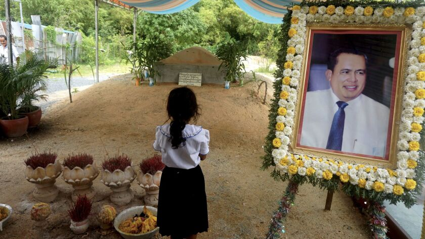 A girl stands beside a portrait of activist Kem Ley at his grave in Ang Takok, Cambodia.