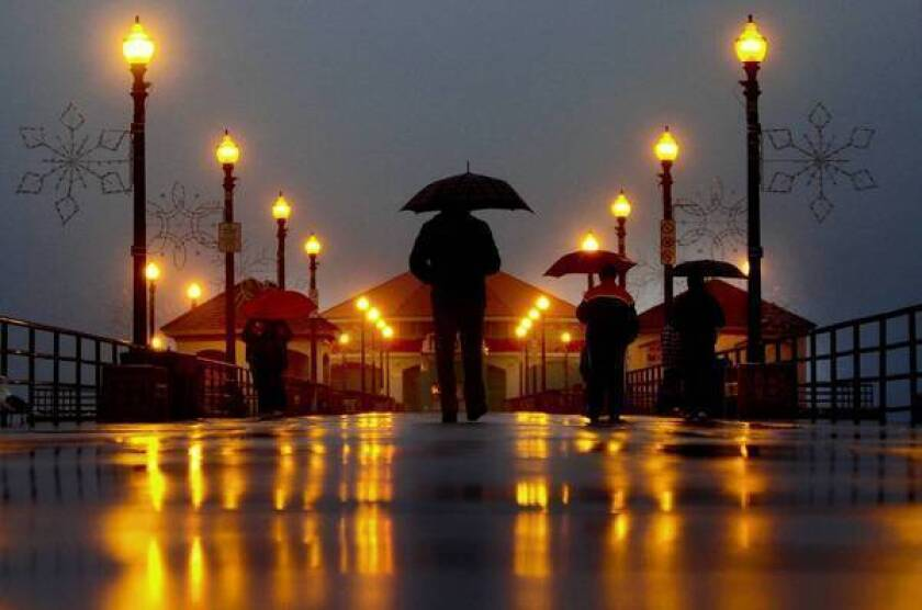 Far removed from the many SigAlerts and traffic accidents caused by the rain, umbrella-toting pedestrians stroll on the Huntington Beach Pier before dawn on Thursday.