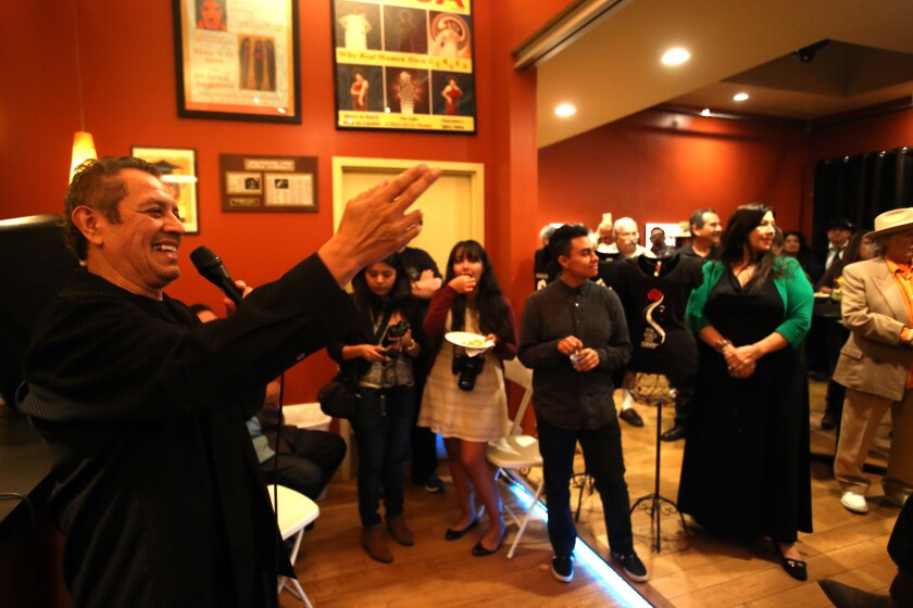 """David Reyes gives the opening statement at the opening of the """"Roots of the Eastside Sound 1955-1965"""" exhibit, which features rare photos and memorabilia from the East L.A. rock 'n' roll scene from Reyes' personal collection at the Jean Deleage Art Gallery in the lobby of the Casa 0101 Theater in Boyle Heights."""