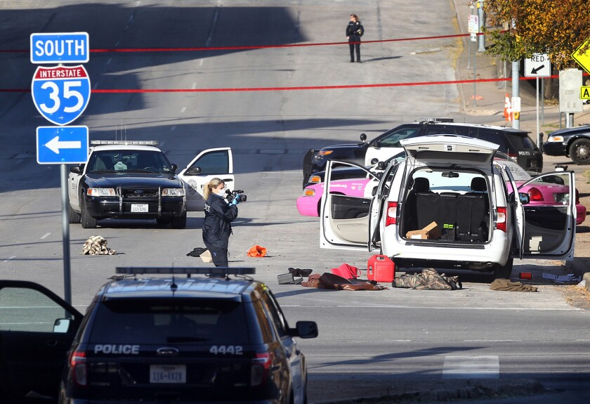 Investigators record the scene where a gunman shot at least 100 rounds into buildings in downtown Austin, including the Mexican consulate and the federal courthouse.