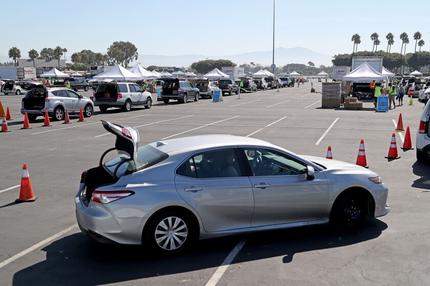 Hundreds of vehicles lineup for free groceries during a drive-through food distribution event at the OC fairgrounds.