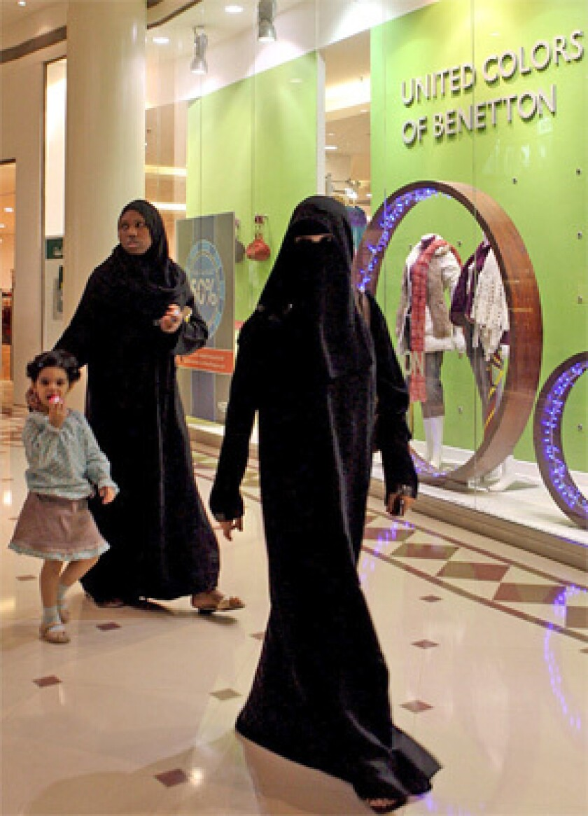 OTHER HALF: Saudi women hang out at a mall in Riyadh. Under the strict Saudi interpretation of Islam, women must be fully covered in public and are not allowed to drive or vote. Wives need their husbands' permission to leave the country.