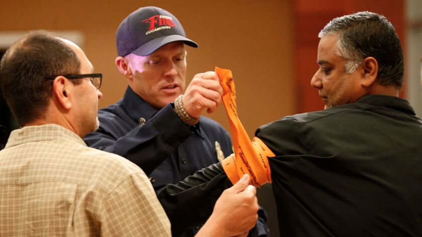 Rancho Cucamonga Fire Capt. Patrick Lewis, center, shows Harlan Medina, left, and Jigish Shah how to wrap a tourniquet.