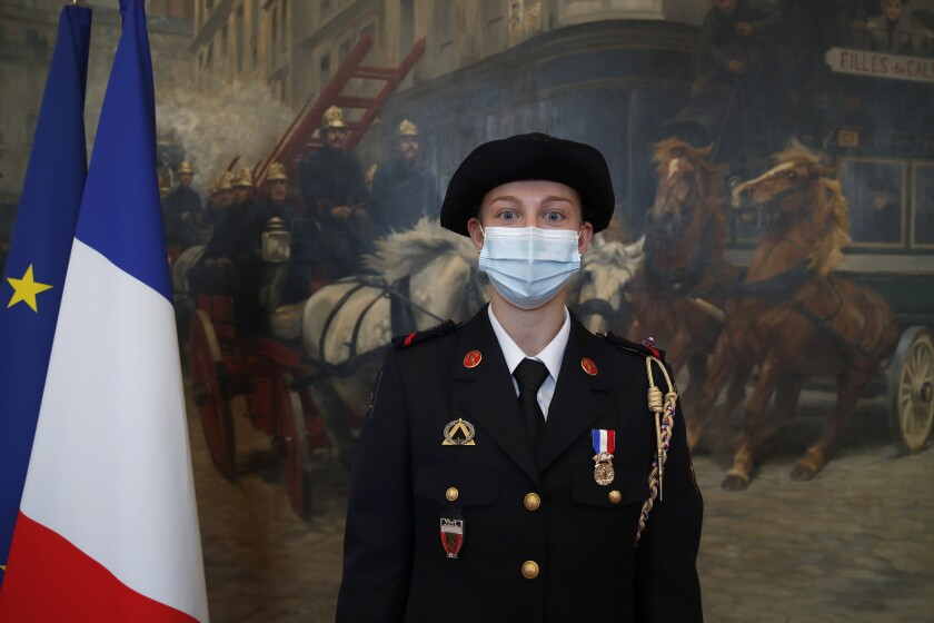 French math teacher-volunteer fighter, Marion Dehecq, poses after she receives a bronze medal for courage and dedication as she used CPR to save the life of a jogger, during a ceremony with France's minister for citizenship issues, Marlene Schiappa at the Paris fire service headquarters in Paris, France, Monday, May 10, 2021. The jogger's wife, Paris-based Associated Press journalist Lori Hinnant, helped identify the anonymous rescuer by putting up thank-you signs in Monceau Park, where her husband Peter Sigal went into cardiac arrest on April 28. (AP Photo/Francois Mori, pool)