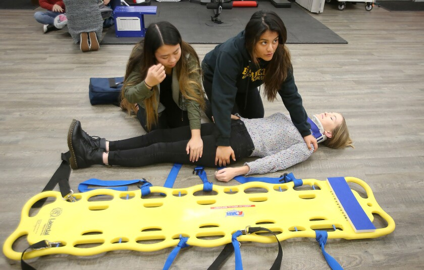 Two students prepare classmate Kenna Cowie to be placed on a backboard as they practice stabilizing a patient with head or neck injuries during an Estancia Medical Academy class Thursday.