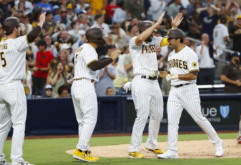 Padres' Daniel Camarena (right) celebrates with teammates after hitting a grand slam Thursday at Petco Park.