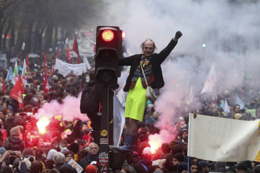 A man stands on a traffic light during a demonstration in Paris